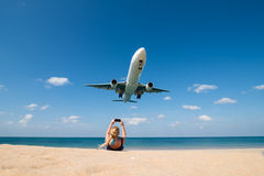 Woman shoot a photo of landing plane on beach Stock Image