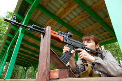 Woman shooting an automatic rifle for strikeball. Young woman aiming at a target and shooting an automatic rifle for strikeball. Focus on the rifle Royalty Free Stock Photography