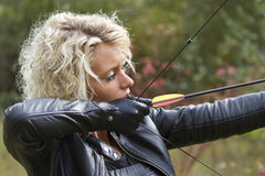 Woman shooting with bow and arrow Stock Image