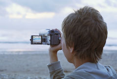 Woman shooting by camcorder. On a beach royalty free stock photo