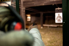 Woman shooting with gun at target in shooting range Royalty Free Stock Photography