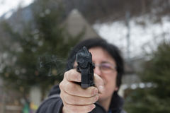 Woman shooting outdoor with a gun Royalty Free Stock Photography