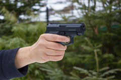 Woman shooting outdoor with a gun Stock Image