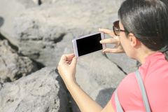 Woman shooting a photo with phone.  Royalty Free Stock Photography