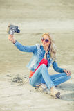 Woman shooting selfie video with old analog camera Stock Image
