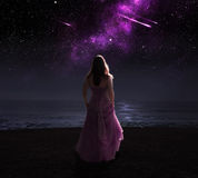Woman and shooting stars. Woman standing in dress at night watching shooting stars Royalty Free Stock Photography