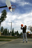 Woman shoots a basketball. A woman has fun trying to make a basket on a playground Royalty Free Stock Image