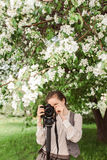 Woman shoots at the camera on a monopod. Woman shoots at the camera on a tripod, monopod against a background of trees, park, apple blossom Royalty Free Stock Image