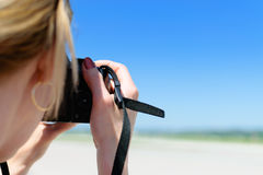 Woman shoots a photo on the beach Royalty Free Stock Photos