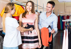 Woman shop assistant offering dress variants to cheerful pair Stock Photography