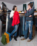 Woman shop assistant showing shirt to man Royalty Free Stock Images
