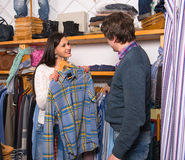 Woman shop assistant showing shirt to man Royalty Free Stock Photography