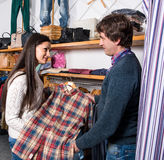 Woman shop assistant showing shirt to man Royalty Free Stock Image