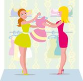 A woman in a shop buying clothes. Woman chooses in shop clothes on the advice of the seller Stock Image