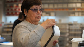 Woman in shop buying a plastic container for food. Stock Photos