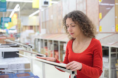 Woman in shop chooses ceramic tile Stock Photo