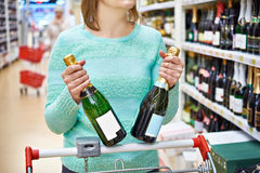 Woman in shop chooses champagne Stock Photos