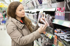 Woman in shop choosing pantyhose from shelves. Caucasian woman in shop choosing pantyhose from shelves Royalty Free Stock Photo