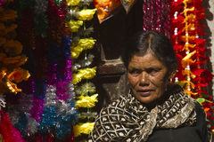 Woman shop keeper in Kathmandu Nepal. She sells colorfull decorations for temples royalty free stock photography