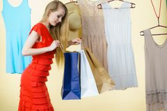 Woman in shop picking summer outfit. Woman in clothes shop store holding shopping bags picking summer perfect outfit, dress hanging on clothing hangers Stock Photos
