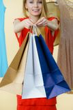 Woman in shop picking summer outfit. Woman in clothes shop store holding shopping bags picking summer perfect outfit, dress hanging on clothing hangers Royalty Free Stock Photos