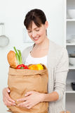 Woman with shoping bags in the kitchen Stock Images