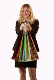 Woman shopper. Attractive blond woman in business attire smiling and holding in front of her four shopping bags Stock Image
