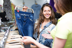 Woman shopper choosing jeans at shop Royalty Free Stock Photos