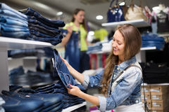 Woman shopper choosing jeans at shop Stock Image