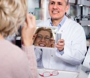 Woman shopper consults with professional male optics on the sele Stock Images