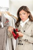 Woman shopper holding empty wallet or purse. While shopping in store. Sad young woman looking at camera in clothing shop stock photos