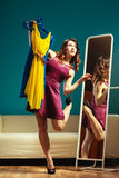 Woman shopper holds hangers with clothes looking in mirror Royalty Free Stock Photos