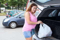 Woman shopper loading bag in trunk of her car on parking. Woman shopper loading bags in trunk of her car on parking stock photo