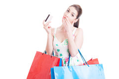 Woman shopper looking surprised holding credit or debit card Stock Image