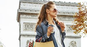 Woman shopper near Arc de Triomphe having coffee and macaroon. Stylish autumn in Paris. trendy woman in trench coat near Arc de Triomphe in Paris, France with Stock Photos