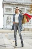 Woman shopper near Arc de Triomphe looking into distance, Paris. Stylish autumn in Paris. Full length portrait of elegant woman in trench coat near Arc de Stock Images