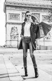 Woman shopper near Arc de Triomphe looking into distance, Paris. Stylish autumn in Paris. Full length portrait of elegant woman in trench coat near Arc de Stock Photos