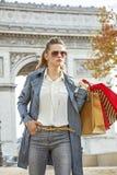 Woman shopper near Arc de Triomphe looking into distance, Paris. Stylish autumn in Paris. trendy woman in trench coat near Arc de Triomphe in Paris, France with Royalty Free Stock Photos