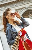 Woman shopper near Arc de Triomphe looking into distance. Stylish Christmas in Paris. smiling elegant woman in trench coat with shopping bags and Christmas Royalty Free Stock Photo