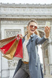 Woman shopper near Arc de Triomphe taking selfie with cellphone Royalty Free Stock Image
