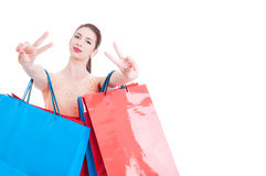 Woman shopper showing victory sign with both hands Stock Photos