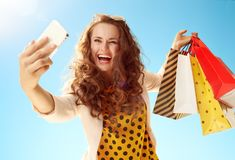 Woman shopper taking selfie with phone against blu Stock Photos
