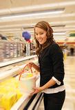 Woman Shopping. Woman selecting ice cream while shopping in the supermarket Royalty Free Stock Image