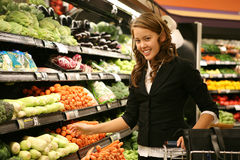 Woman Shopping. A pretty woman shopping for vegetables in the supermarket Stock Photos