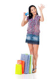 Woman shopping. Beautiful young woman with shopping bags showing credit card or gift card, isolated over white background Stock Photos