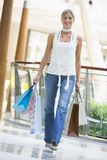 Woman Shopping. Woman in shopping mall carrying bags Royalty Free Stock Images