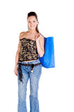 Woman Shopping. Mid adult woman in a black and gold corset and blue jeans  carrying a large shopping bag over her shoulder Royalty Free Stock Photos