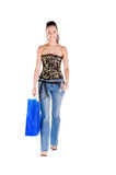 Woman Shopping. Mid adult woman in a black and gold corset and blue jeans walking and carrying a large shopping bag Stock Photography