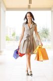 Woman and shopping. Young woman with bags in shopping center, smiling and  walking Stock Images