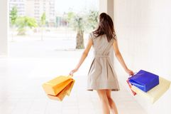 Woman and shopping. Young woman with bags in shopping center, smiling and  walking Stock Image